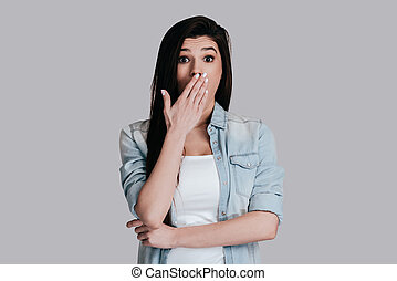 No way! Surprised attractive young woman in jeans wear covering mouth with hand and looking at camera while standing against grey background