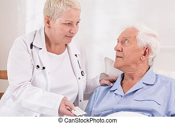 Nurse giving pills to senior patient