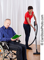 Nurse helping disabled with cleaning