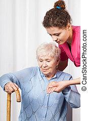 Nurse helping woman get up