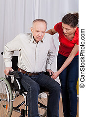 Nurse helps to get up disabled