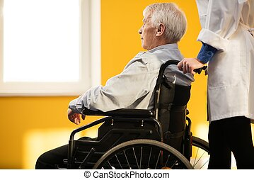Nurse woman with senior man in wheelchair r