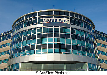 Modern glass office building with a for lease sign on it
