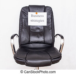 Office chair on which a piece of paper with the inscription business strategy management concept and types of corporate-level strategies, business planning and decision making
