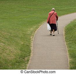 Elderly female with walking stick on deserted, winding path. Plenty of space to add text.