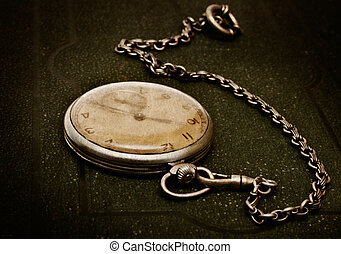 Very old clock with chain lying on rough green surface - shallow depth of field