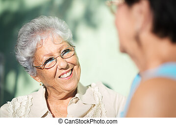 Active retirement, two elderly female friends talking on bench in public park