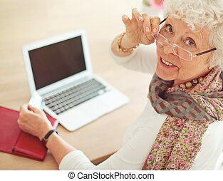 Old Woman in front of Her Laptop Looking at You