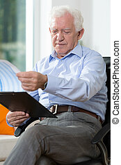 Older man reading notes