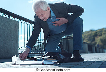 Older man with severe heart pain picking up documents
