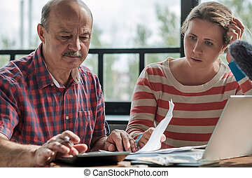 Olderly Spanish man counting money with his daughter.