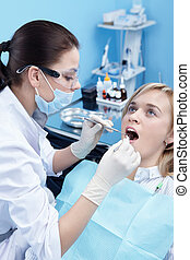 The dentist examines a patient
