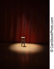 empty stool on stage of a theater, concert or comedy show lighted by a single spotlight in front of a red curtain.