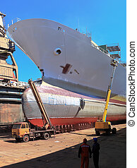 A large cargo ship is being renovated in shipyard.
