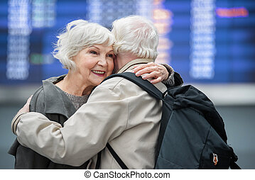 Optimistic old husband and wife are embracing with love