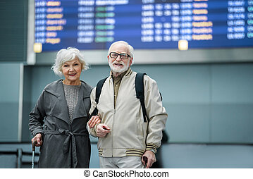 Optimistic old wife and husband are posing with smile