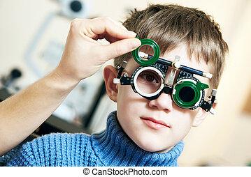 Optometrist doctor examines eyesight of child boy with phoropter