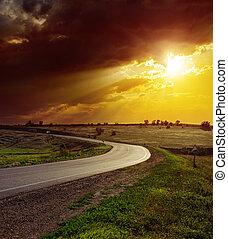 orange dramatic sunset over asphalt road