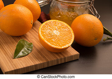 orange fruit on wooden panel with jam in a glass bowl
