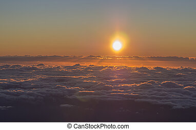 orange red sunrise, sun rising above the fluffy clouds with sunbeam rays and lens flare, taken from top of pico del teide tenerife