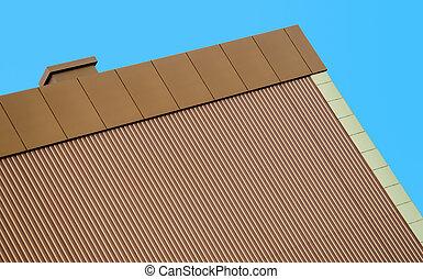 orange wall of a modern building against a blue sky