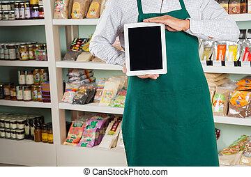 Owner Showing Digital Tablet In Store