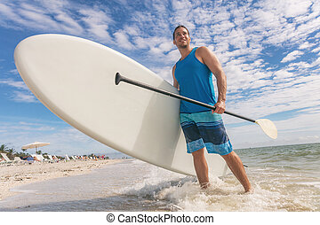 Paddle board fun SUP watersport fitness man carrying paddleboard after water surf session in Sanibel Island, Florida. USA summer travel fit active lifestyle