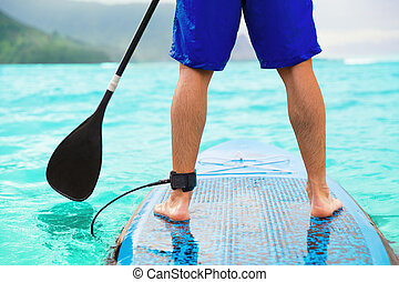 Paddle board man doing stand-up paddleboard on ocean. Athlete paddleboarding on SUP surf board on Hawaii beach travel. Closeup of legs standing on board