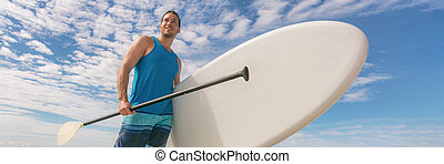 Paddle board SUP fit man carrying paddleboard on hawaii beach banner panorama. Fitness active lifestyle fun activity outdoors athlete