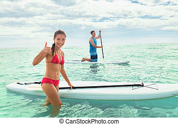 Paddleboard beach people on stand-up paddle boards surfing in ocean on Hawaii beach. Mixed race couple woman and Caucasian man enjoying watersport