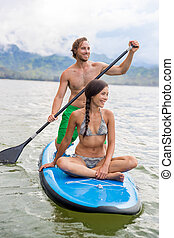Paddleboard couple having fun paddleboarding together on Hawaii beach vacation summer holidays. Woman sitting on board while man paddles
