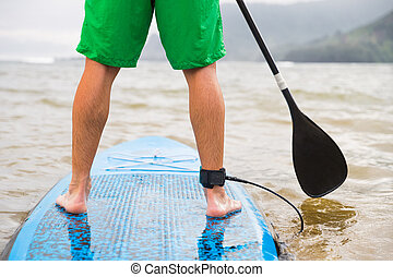 Paddleboard man paddling on SUP stand up paddle board on lake. Closeup of feet and legs