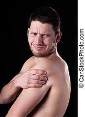 Young man suffering from pain of rotator cuff