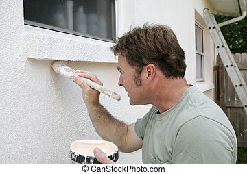 A painter edging around an exterior window with a brush.