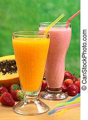 Papaya juice and strawberry milkshake with straws (Selective Focus, Focus on the straw in the papaya juice)
