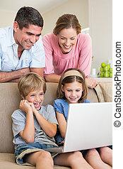 Parents watching children using laptop