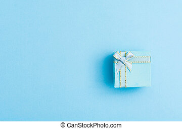 Pastel blue holiday background with blue gift box with bow. Flat lay