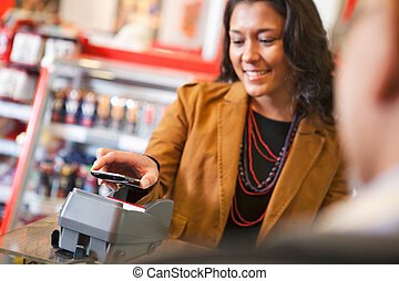 Young woman paying for purchase with cell phone
