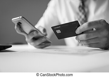 Payment of goods online. Online trading on the currency exchange. Smartphone and Internet Commerce. Online payments through the phone. Young businessman with a bank credit card in his hands.