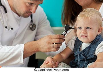 Pediatrician checking girl ears