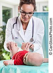 Pediatrician examining little baby