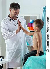 Pediatrician giving boy a five