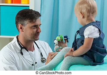 Pediatrician making baby laugh