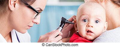 Pediatrician using otoscope