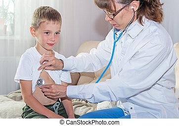 Pediatrician woman doctor examining boy by stethoscope.