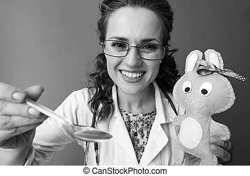 pediatrician woman giving children's suspension while distracting child with toy