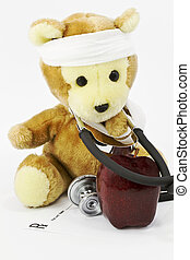 Apple with toy bear, gauze wrapped about its head and stethoscope around its neck