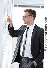 pensive businessman looking in office window