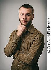 pensive young man with beard looking at camera