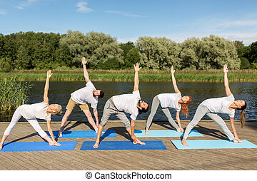 people making yoga in left triangle pose outdoors